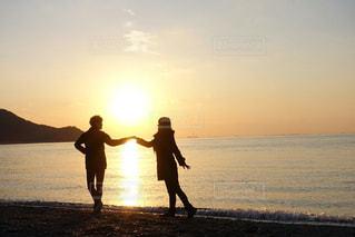 ビーチの上を歩く女と男の写真・画像素材[1320986]