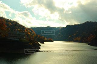 背景の山が付いている水の体の上に行く橋 - No.808661