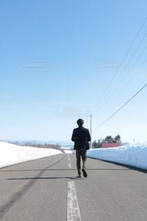 雪の側をスケート ボードに乗って男覆われた斜面 - No.1074100