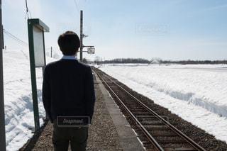雪の中で線路上に立っている男 - No.1074103