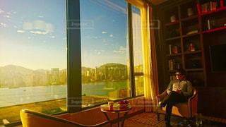 窓の前のテーブルに座っている人の写真・画像素材[1188136]