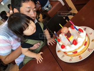 ケーキでテーブルに座っている少女の写真・画像素材[732867]
