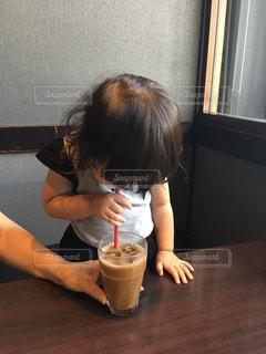 小さな女の子のテーブルに座っての写真・画像素材[739088]