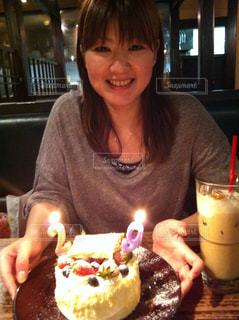 誕生日ケーキの前のテーブルに座っている女性の写真・画像素材[747456]