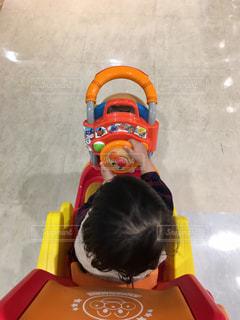 プラスチックのおもちゃに坐っていた男の写真・画像素材[815115]