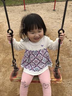 バットを保持しているホーム プレートの横に立っている女の子の写真・画像素材[870586]