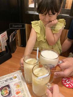 コーヒーを飲みながらテーブルに座っている小さな女の子の写真・画像素材[2344831]