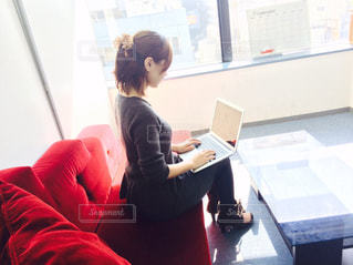 コンピューターの前に座っている女性の写真・画像素材[1441029]