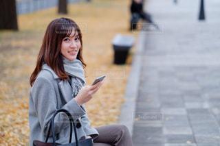 歩道に座っている女性の写真・画像素材[2884656]