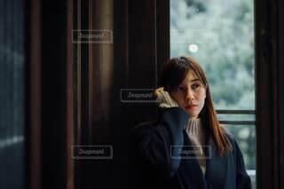 窓の前に立っている女性の写真・画像素材[3817232]