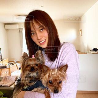 カメラのポーズをとる犬を抱いている女性の写真・画像素材[4639771]