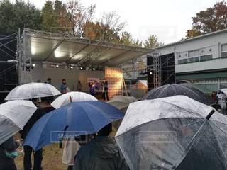 雨の中を歩いている人々のグループが傘を持っているの写真・画像素材[3496307]