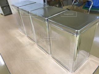 テーブルの上に座っている銀のブリキ缶の写真・画像素材[819195]