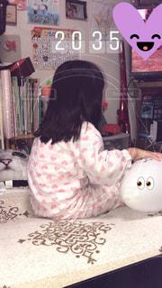ベッドの上で座っている女の子の写真・画像素材[1122317]