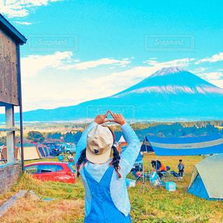 山の前に立っている間凧を保持している女性の写真・画像素材[849516]
