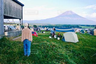 草で覆われた丘の上の緑のテントの前に立っている男の写真・画像素材[869716]
