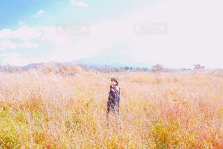 乾いた草のフィールドに立っている人の写真・画像素材[869717]
