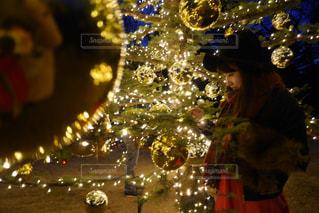 眼鏡をかけてクリスマス ツリーの横に座っている女性の写真・画像素材[912569]