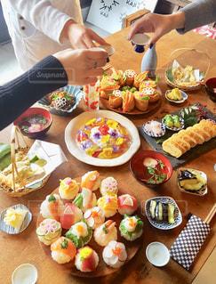 食品のプレートをテーブルに座っている女性の写真・画像素材[987405]