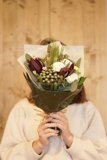 花の花瓶とテーブルに座っている女性の写真・画像素材[1784338]