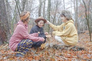 木の隣に座っている幼い子供のグループの写真・画像素材[2791474]