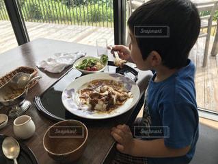 食品のプレートをテーブルに座って若い男の子の写真・画像素材[1299858]