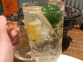 テーブルにビールのグラスを持っている手の写真・画像素材[707005]
