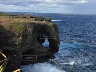 水の体の横にある岩の上に座っている人の写真・画像素材[979366]