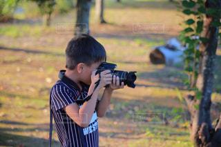 一眼レフを持つ少年の写真・画像素材[715933]
