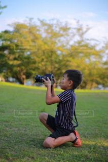 芝生で写真を撮ろうとしている少年の写真・画像素材[715934]