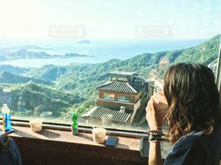 山の前にあるベンチに座っている人の写真・画像素材[792192]
