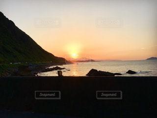 背景の山が付いている水の体に沈む夕日 - No.792193