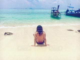 水の体の横にある砂浜に座る人の写真・画像素材[873451]