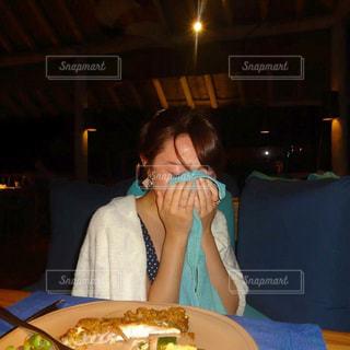 食品のプレートをテーブルに座っている女性の写真・画像素材[745029]