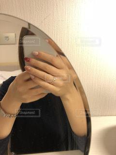 カメラにポーズ鏡の前に座っている人の写真・画像素材[1016336]