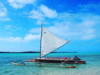 水の体の横に座っている青と白のボートの写真・画像素材[1075060]