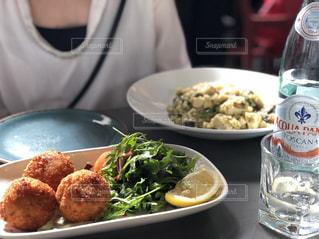 食品のプレートをテーブルに座っている女性の写真・画像素材[1159994]