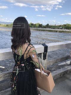 水の近くのベンチに座っている女性の写真・画像素材[923168]