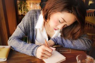 テーブルに座ってメモを取っている女性 - No.1103947