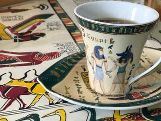 エジプト壁画柄のコーヒーカップとソーサーに入ったホットコーヒーの写真・画像素材[1390200]