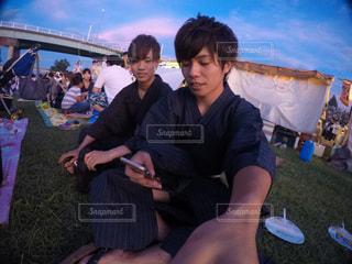 草の中に座っている人々 のグループの写真・画像素材[1038146]