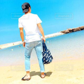 水の体の横に立っている人の写真・画像素材[1038149]