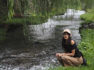 川の隣に座っている人の写真・画像素材[1038196]