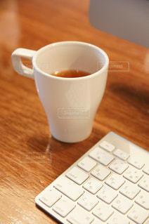 コーヒーカップとキーボードの写真・画像素材[597055]