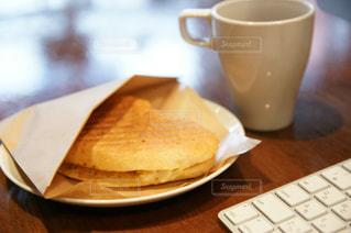 キーボードのそばに置いたパニーニとコーヒーカップの写真・画像素材[597057]