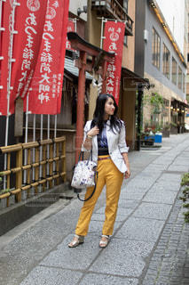 神社のある小道に佇む女性の写真・画像素材[2581992]