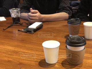 コーヒーを飲みながらテーブルに座っている人の写真・画像素材[2904407]