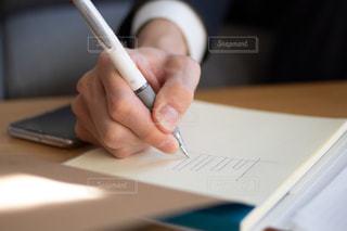 紙にグラフを描いている人の写真・画像素材[2952564]