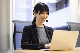 ラップトップを使ってテーブルに座っている女性の写真・画像素材[3060327]