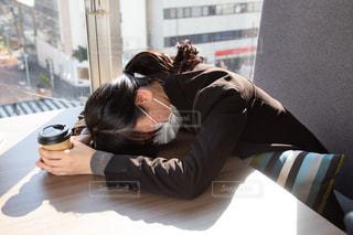 テーブルに突っ伏すマスクの女性の写真・画像素材[3064791]